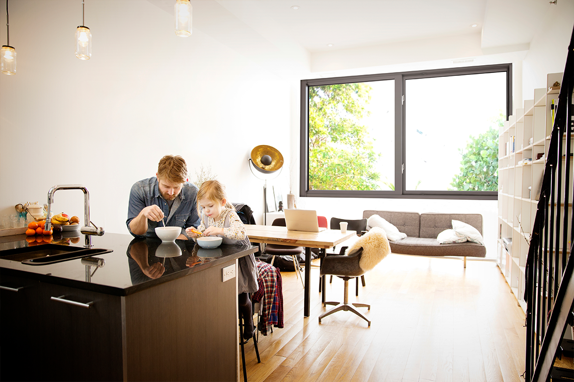 Man and daughter enjoying breakfast in room with impact resistant, noise reducing windows